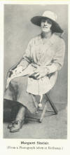 Margaret Sinclair sitting with coat and hat